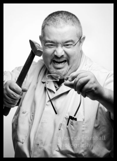 Optical workshop team member poses with a hammer over a pair of glasses