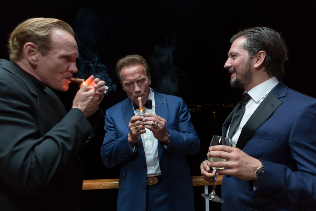 Arnold Schwarzenegger lights a cigar with two friends at a party