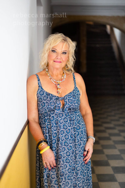 Portrait of opera singer Karita Mattila wearing a blue dress, posing in a hallway