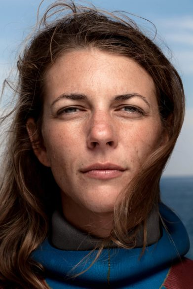 Close-up portrait of woman in a wetsuit with the sea in the background