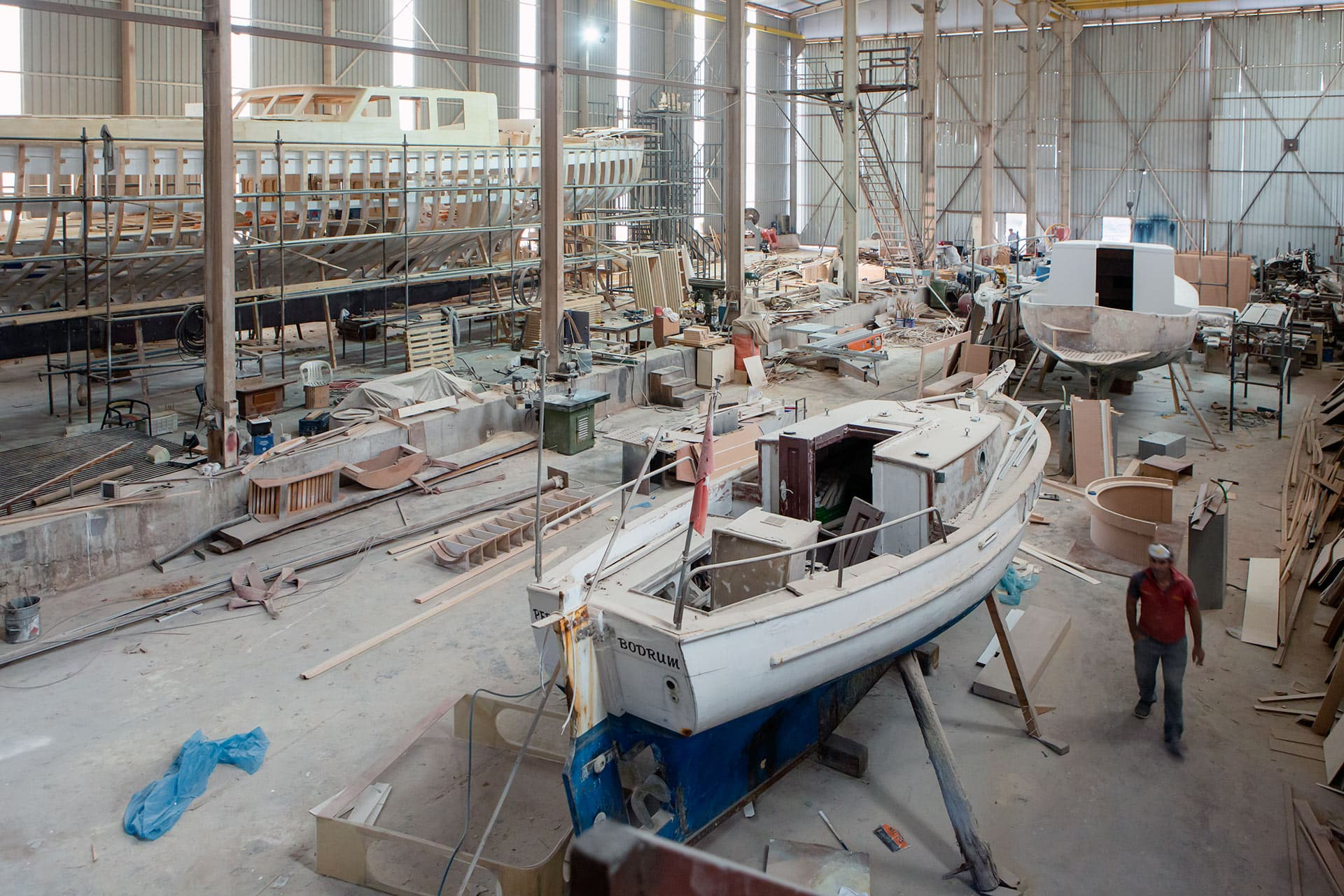Wide view of the interior of a boatyard hangar with 3 boats visibly under construction