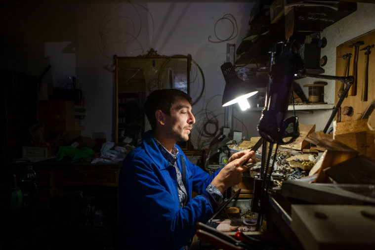 Man in a blue overall coat sits in a dark workshop under a lamp making jewellery