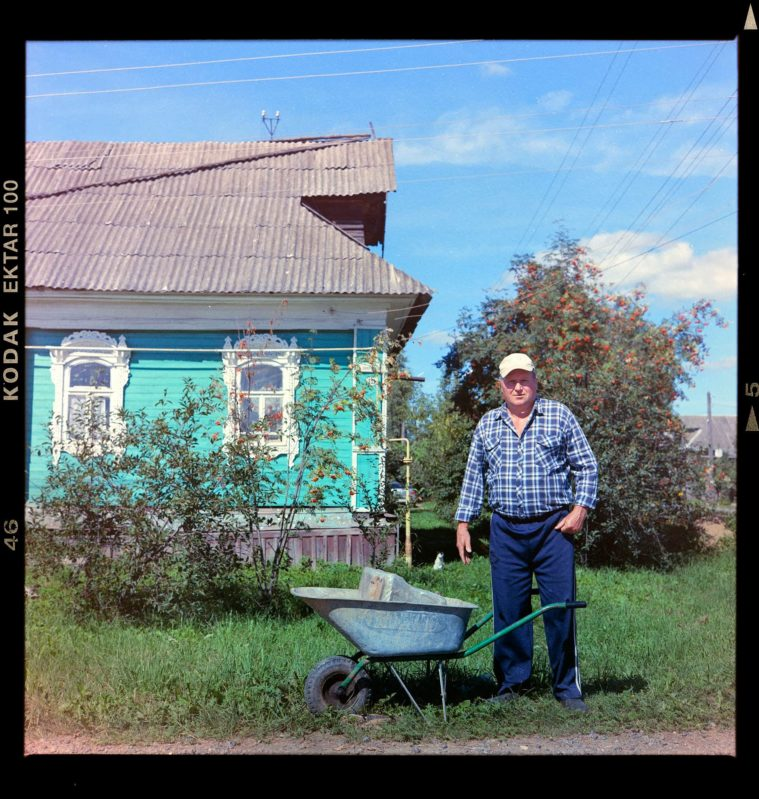Photograph of a middle-aged man standing besided a wheelbarrow in the garden of his turquoise wooden house
