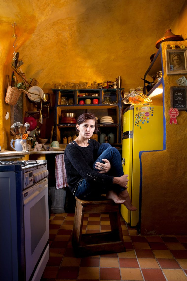 A woman hugs her knees sitting on a low wooden stool in a yellow kitchen