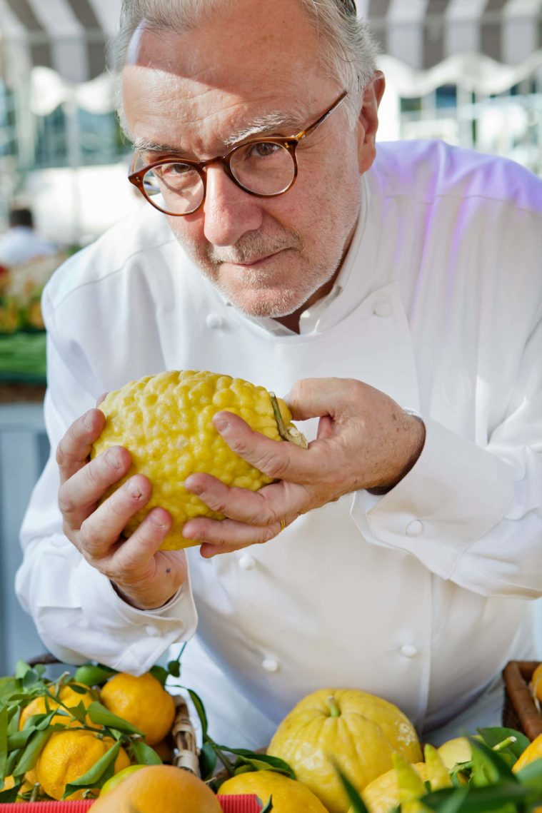 Close-up photograph of a chef holding a large yellow citrus fruit over a market stall display of lemons