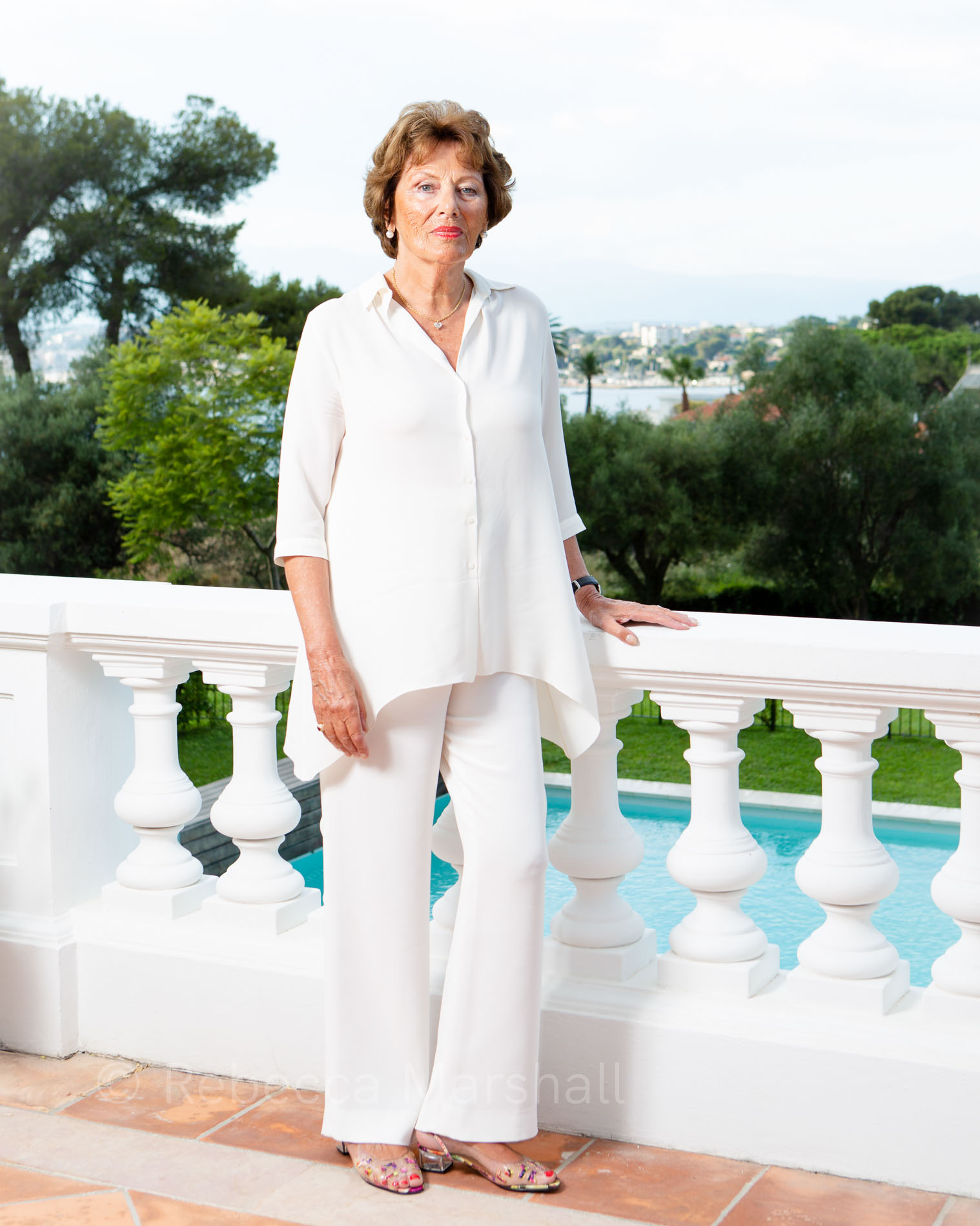 Full-length portrait of a woman in a white trouser suit standing on a terrace overlooking a swimming pool