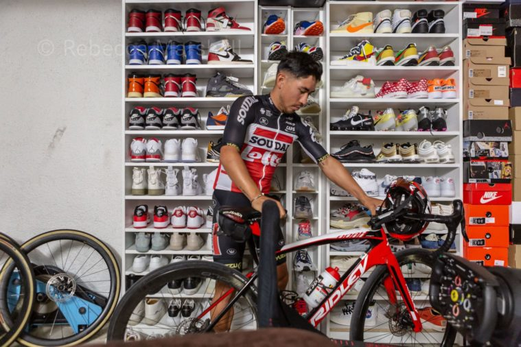 Cyclist Caleb Ewan parking his bike in his bike room, in front of a wall of trainers