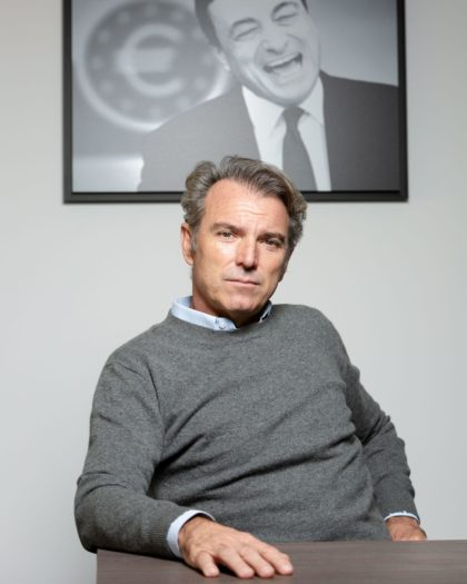 Portrait of a man in a shirt and grey jumper sitting in front of a framed picture of Mario Draghi on the wall behind