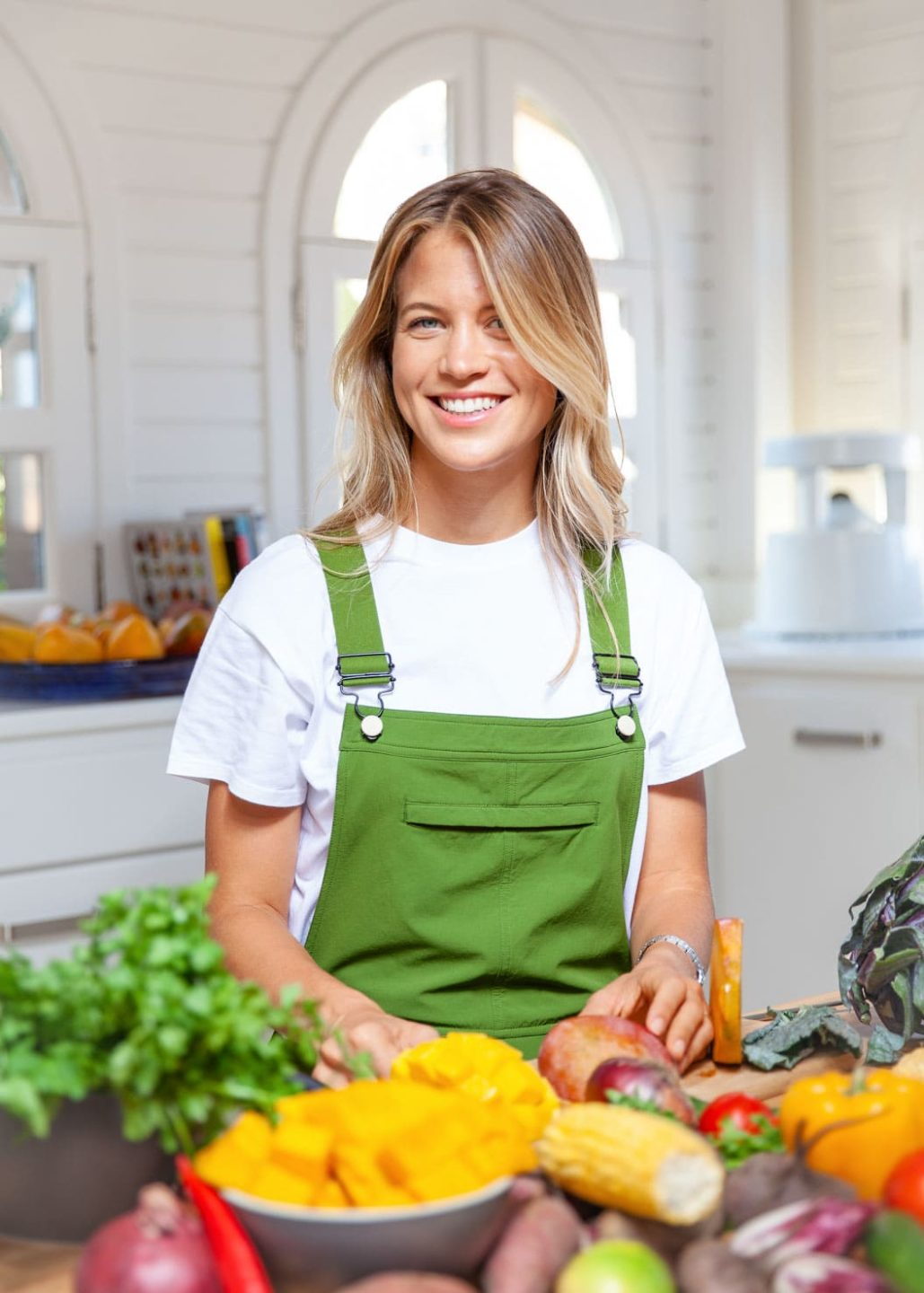 Young blonde woman wearing a white t-shirt and green dugarees smiles to the camera standing behind a table piled with colourful fresh fruit and vegetables