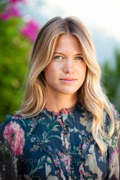 Portrait of a young blonde woman wearing a patterned floral dress, out-of-focus flowers in the background