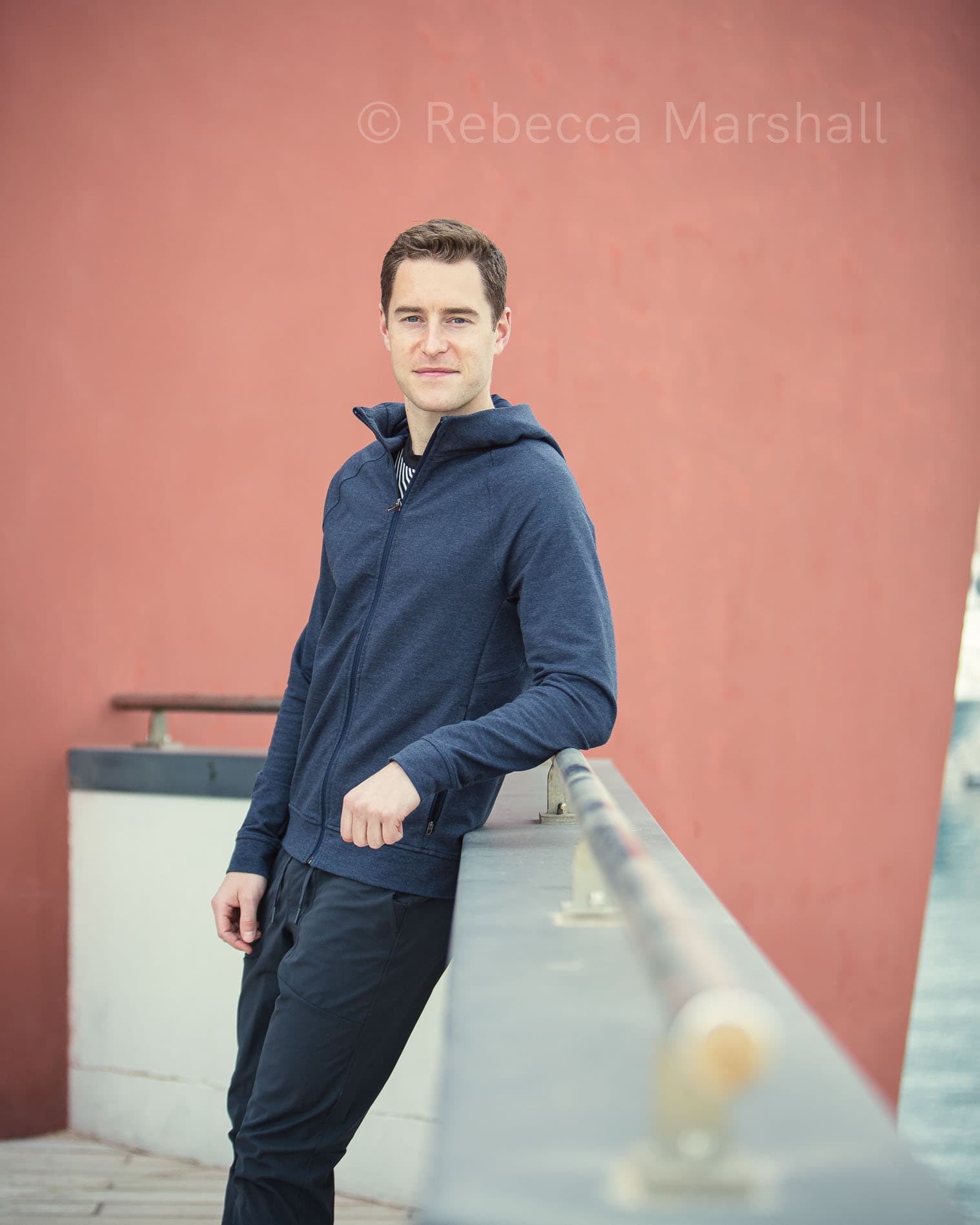 Portrait of a man in a blue tracksuit leaning on a railing in front of a red wall
