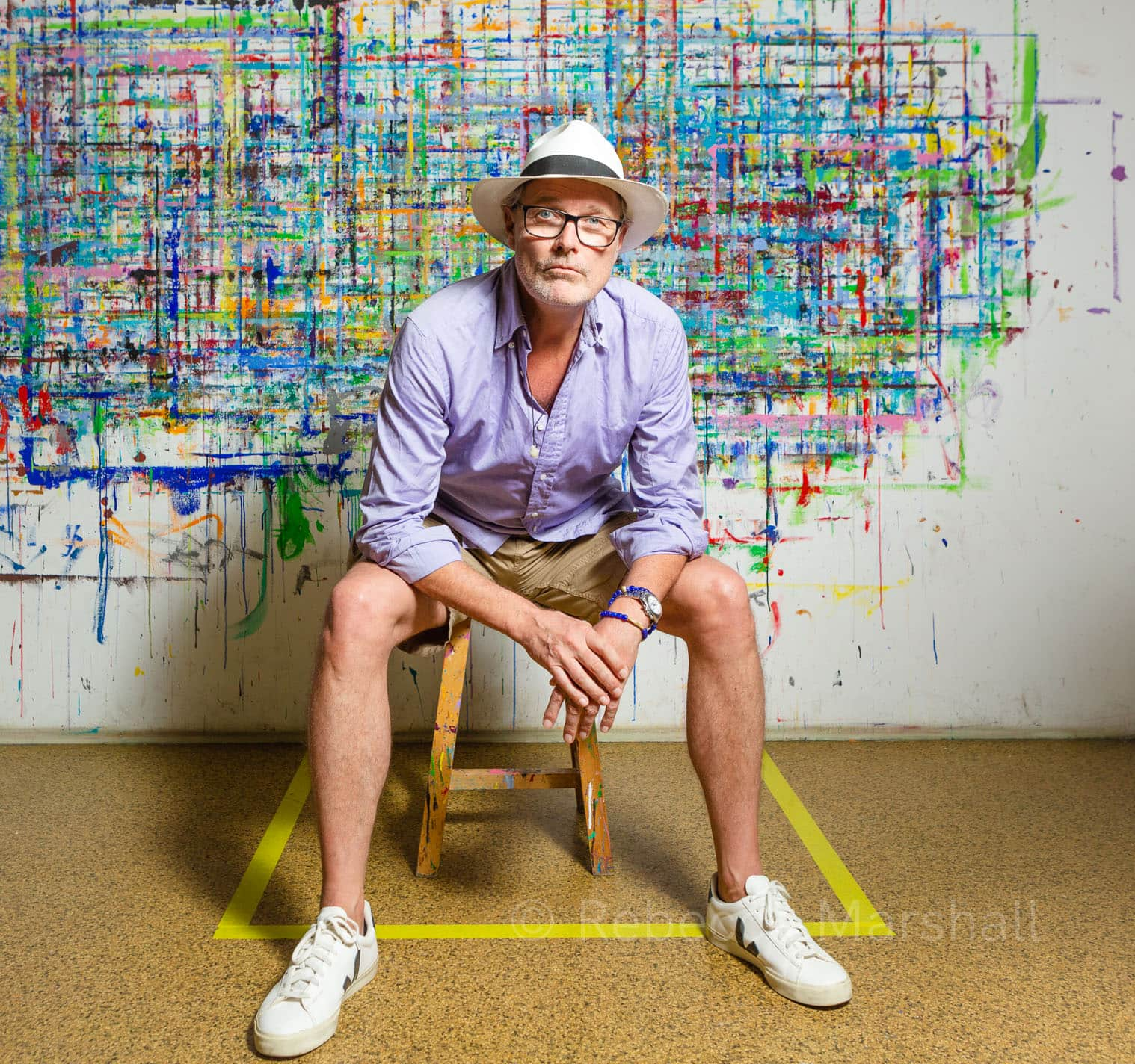 Portrait of a man wearing a white hat and sitting in front of a modern artwork