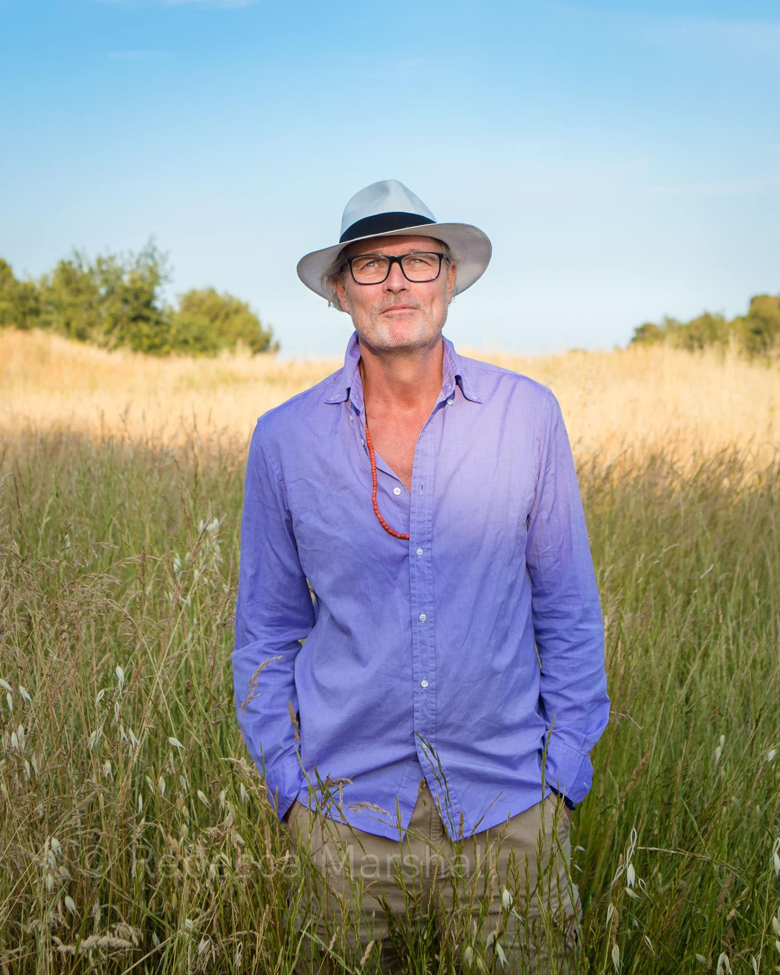 Photographic portrait of a man standing in a cornfield in a white hat and purple shirt
