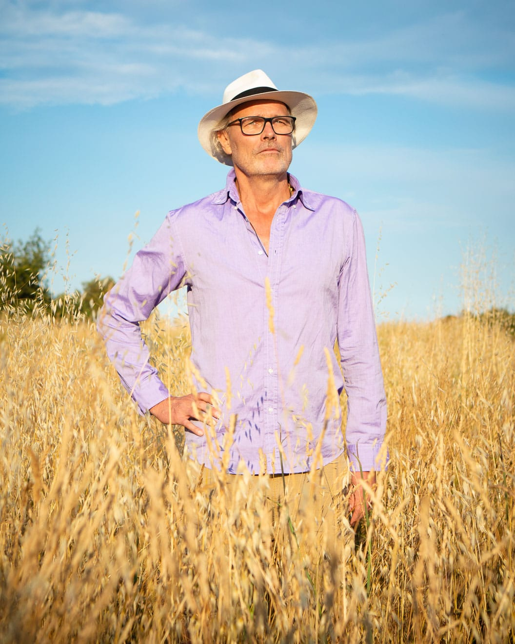 Photographic portrait of a man standing in a cornfield in a white hat