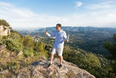 Photo of a man standing on a rock at the top of a hill making a video of himself